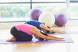 Two fit women bending over on exercise mats in fitness studio