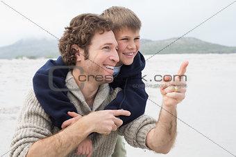 Man piggybacking his son at beach