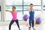 Two sporty women stretching hands at yoga class