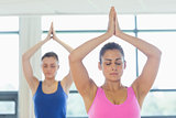 Two women in Namaste position with eyes closed at fitness studio