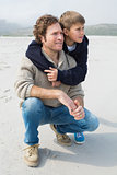 Casual man and son relaxing at beach