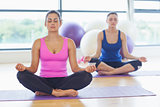 Two sporty women in lotus pose at fitness studio