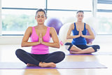 Two sporty women sitting with joined hands at fitness studio
