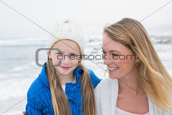 Cute girl with smiling mother relaxing at beach