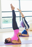 Fit women doing the shoulder stand posture in fitness studio