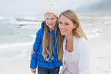 Cute girl with smiling mother at beach