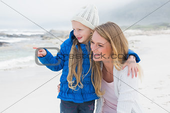 Girl showing something to mother at beach