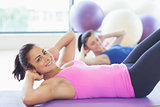 Two fit young women doing pilate exercises