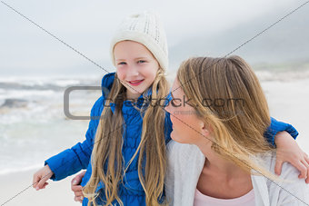 Cute young girl with smiling mother at beach