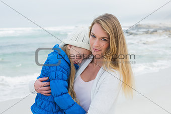 Young woman carrying little girl at beach
