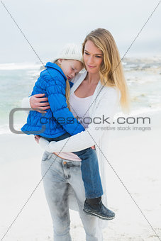 Woman carrying her little girl at beach