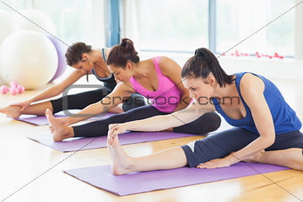 Fit class stretching legs on mats at yoga class