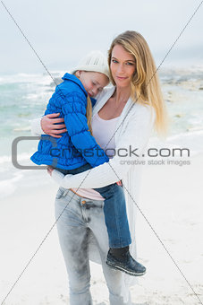 Young woman carrying her little girl at beach