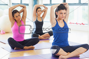 Class stretching hands behind heads on mats at yoga class