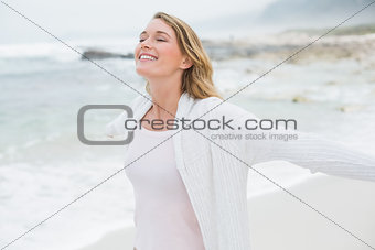 Casual woman with eyes closed stretching hands at beach