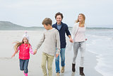Happy family of four walking at beach