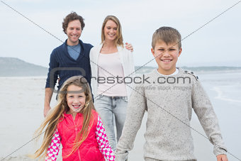 Happy family of four at the beach