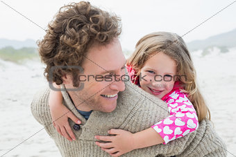 Man piggybacking his daughter at beach