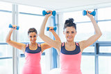 Two fit women lifting dumbbell weights in gym