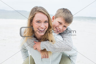 Woman piggybacking her son at beach