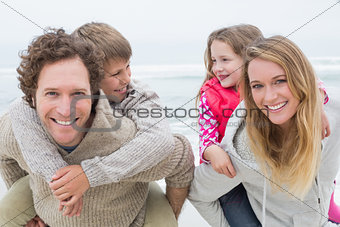 Happy couple piggybacking kids at beach