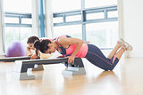 Two women performing step aerobics exercise in gym