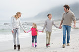 Happy family of four walking hand in hand at beach