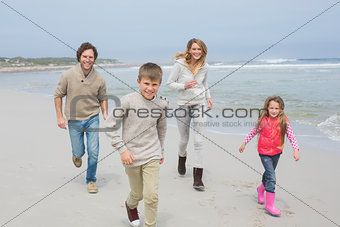 Happy family of four running at beach