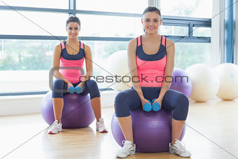 Two fit women with dumbbells on fitness balls in gym