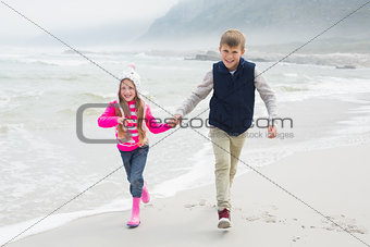 Happy brother and sister walking hand in hand at beach
