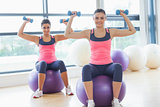 Two fit women exercising with dumbbells on fitness balls