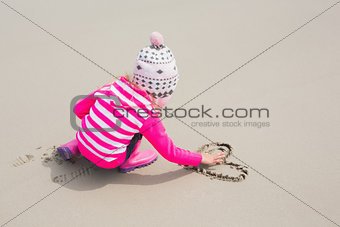Girl in warm clothing drawing heart shape on sand at beach