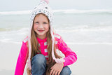Cute little girl in warm clothing at beach