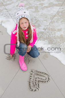Little girl with drawn heart shape on sand at beach