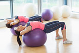 Two fit women stretching on fitness balls in gym