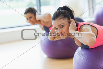Portrait of two fit women exercising on fitness balls