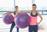 Two fit young women holding exercise balls at gym