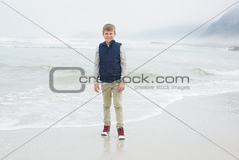 Full length of a cute smiling boy at beach