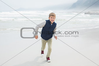Cute smiling boy running at beach