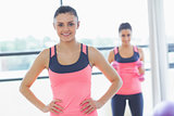 Smiling fit woman with friend in background at exercise room