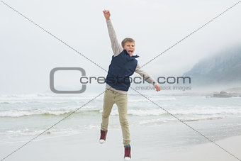 Full length of a casual boy jumping at beach