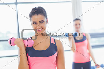 Fit woman lifting dumbbell weights with friend in background at gym