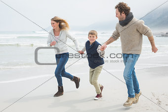 Happy family of three running at beach