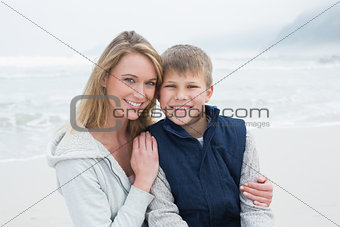 Cute boy with smiling mother at beach