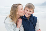 Mother kissing boy at beach