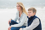 Casual woman and son relaxing at beach