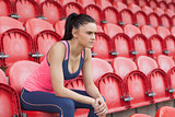 Serious toned young woman sitting on chair in the stadium