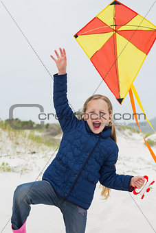 Cheerful young girl with kite at beach