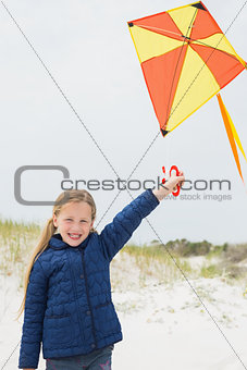 Portrait of a smiling girl with kite at beach