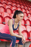 Serious toned woman sitting on chair in the stadium